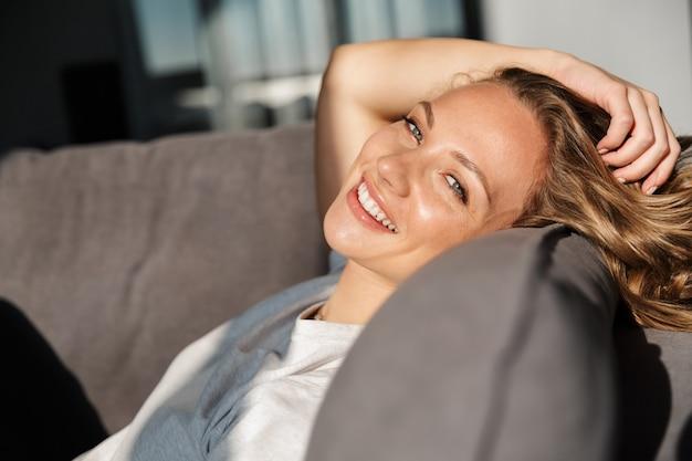 Uśmiechnięta ładna blondynka młoda kobieta nosząca zwykłe ubrania, relaksująca się na kanapie w domu