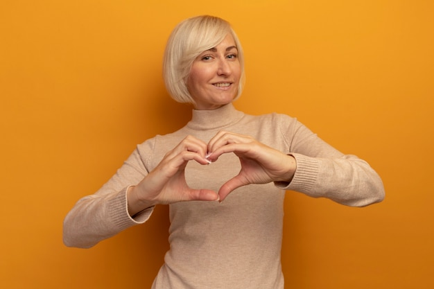 Uśmiechnięta ładna blondynka słowiańska gestykuluje serce ręka znak na białym tle