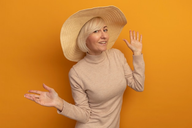 Uśmiechnięta ładna blondynka słowiańska kobieta z kapeluszem plażowym stoi z uniesionymi rękami na pomarańczowo