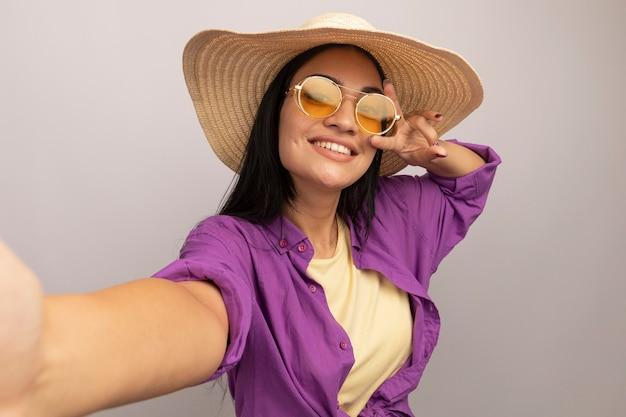 Uśmiechnięta ładna brunetka kaukaska dziewczyna w okularach przeciwsłonecznych z kapeluszem plażowym gestykuluje ręką znak zwycięstwa i udaje, że trzyma aparat, biorąc selfie na białym tle