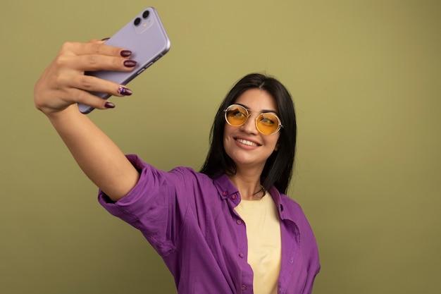 Uśmiechnięta ładna brunetka kobieta w okularach przeciwsłonecznych trzyma i patrzy na telefon, biorąc selfie na białym tle na oliwkowej ścianie
