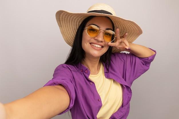 Uśmiechnięta ładna brunetka kobieta w okularach przeciwsłonecznych w kapeluszu plażowym, gestykuluje trzy palcami i udaje, że trzyma przód, biorąc selfie na białej ścianie