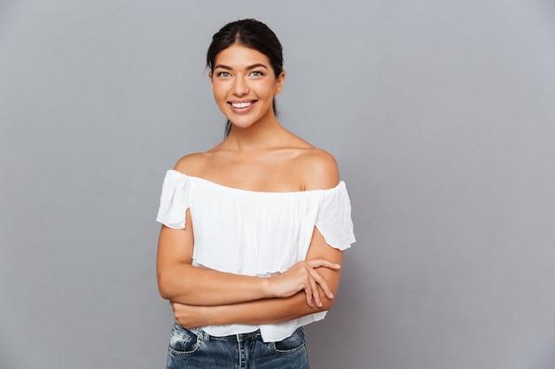 Uśmiechnięta ładna brunetka stojąca ze złożonymi rękami i patrząca na przód odizolowana na szarej ścianie