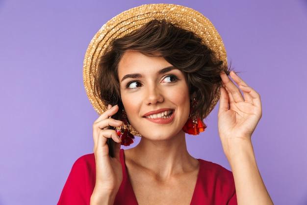 Uśmiechnięta ładna brunetki kobieta w sukni i słomianym kapeluszu