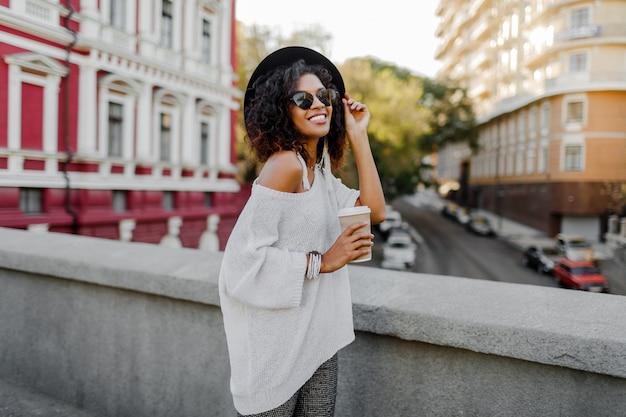 Uśmiechnięta ładna czarna kobieta w białym swetrze i czarnym kapeluszu trzyma filiżankę kawy.
