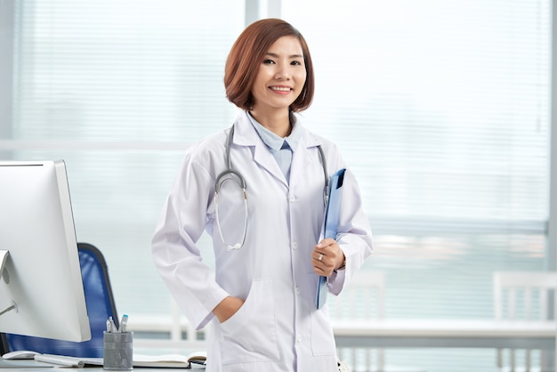 Uśmiechnięta ładna doktorska pozycja w szpitalnym biurze z papierową falcówką