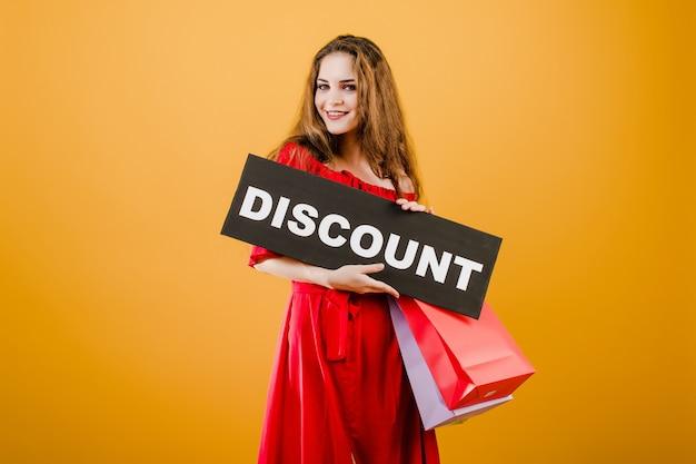 Uśmiechnięta ładna dziewczyna ma znak zniżki z kolorowe torby na zakupy na białym tle nad żółtym
