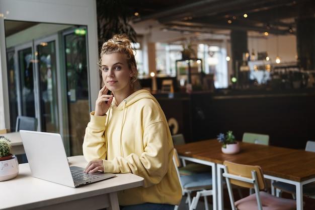 Uśmiechnięta ładna dziewczyna patrząc na kamery siedząc w kawiarni, pracując na laptopie.