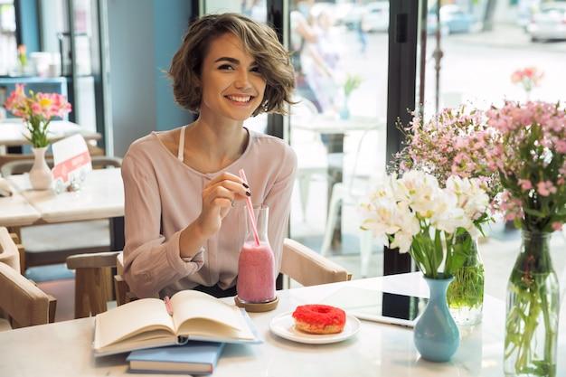 Uśmiechnięta ładna dziewczyna pije smoothie z słomą