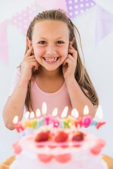 Uśmiechnięta ładna dziewczyna stoi blisko urodzinowego torta