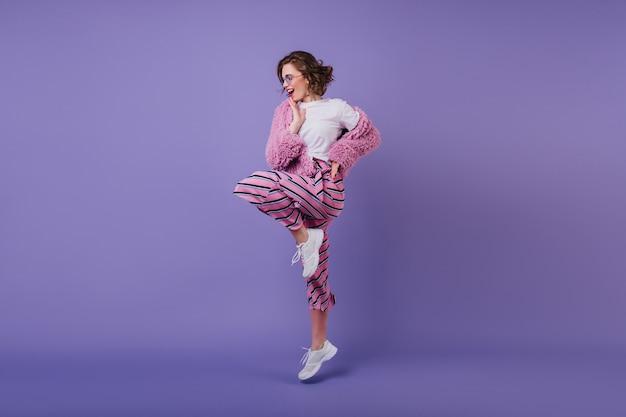 Uśmiechnięta ładna dziewczyna z falistą fryzurą stojącą na jednej nodze na fioletowej ścianie. wesoła brunetka modelka tańczy w białych trampkach.