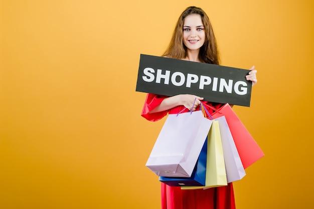 Uśmiechnięta ładna dziewczyna zakupy znak z kolorowymi torba na zakupy odizolowywającymi nad kolorem żółtym