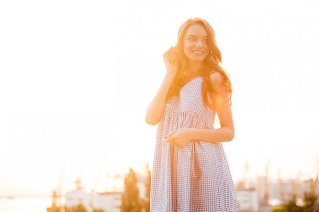 Uśmiechnięta ładna imbirowa kobieta w smokingowej słuchającej muzyce