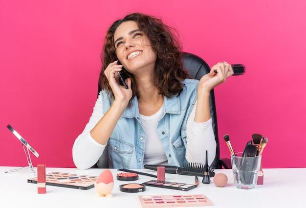 Uśmiechnięta ładna kaukaska kobieta siedzi przy stole z narzędziami do makijażu rozmawiając przez telefon i trzymając grzebień odizolowany na różowej ścianie z miejscem na kopię