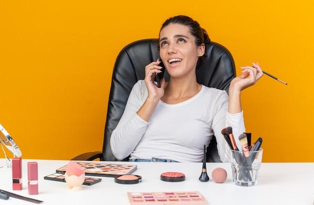 Uśmiechnięta ładna kaukaska kobieta siedzi przy stole z narzędziami do makijażu, rozmawiając przez telefon, trzymając pędzel do makijażu i patrząc w górę