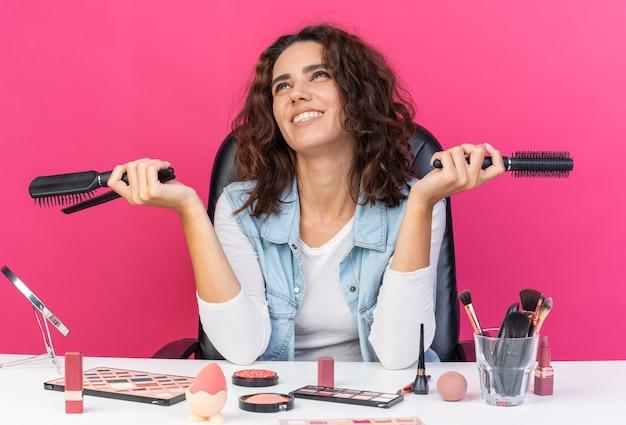 Uśmiechnięta ładna kaukaska kobieta siedzi przy stole z narzędziami do makijażu, trzymając grzebienie i patrząc na bok
