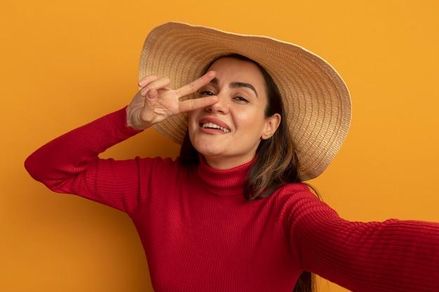 Uśmiechnięta ładna kaukaska kobieta w kapeluszu plażowym gestykuluje ręką znak zwycięstwa i udaje, że trzyma aparat na pomarańczowo