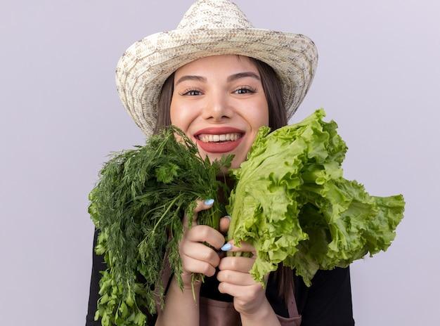 Uśmiechnięta ładna kaukaska ogrodniczka w kapeluszu ogrodniczym trzymająca bukiet koperku i sałatki