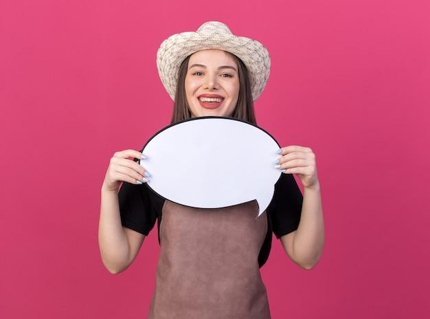Uśmiechnięta ładna kaukaska ogrodniczka w kapeluszu ogrodniczym trzymająca dymek na różowej ścianie z miejscem na kopię
