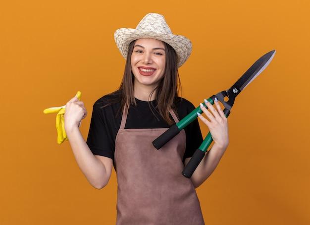 Uśmiechnięta ładna kaukaska ogrodniczka w kapeluszu ogrodniczym, trzymająca nożyczki ogrodnicze i rękawiczki odizolowane na pomarańczowej ścianie z miejscem na kopię
