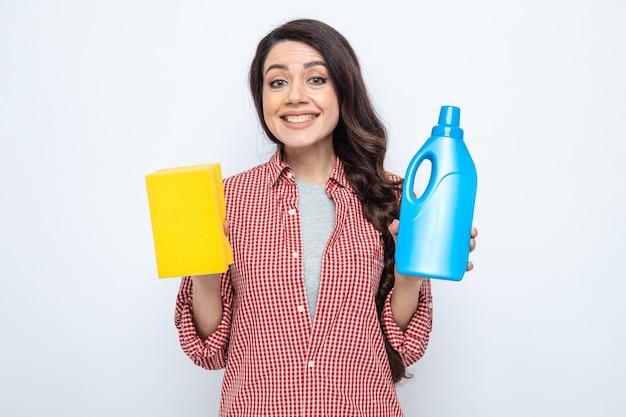 Uśmiechnięta ładna kaukaska sprzątaczka trzyma płyn do czyszczenia toalet i gąbkę