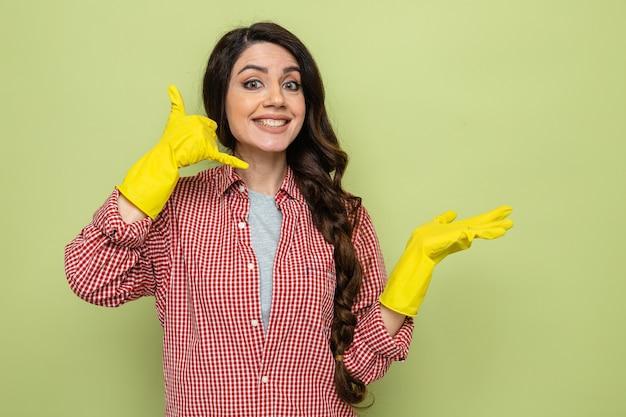 Uśmiechnięta ładna kaukaska sprzątaczka w gumowych rękawiczkach trzymająca otwartą dłoń i gestykulująca zadzwoń do mnie znak