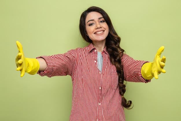 Uśmiechnięta ładna kaukaska sprzątaczka w gumowych rękawiczkach trzymająca otwarte ręce