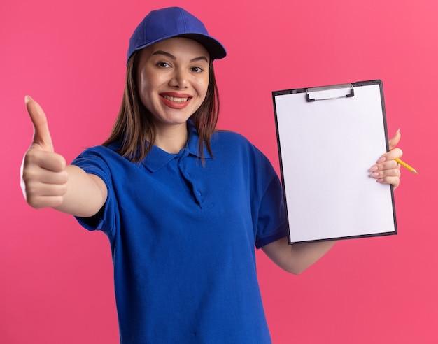 Uśmiechnięta ładna kobieta dostawy w mundurze posiada schowek i kciuki do góry na białym tle na różowej ścianie z miejsca na kopię