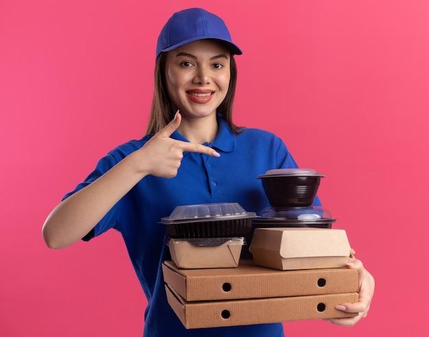 Uśmiechnięta ładna kobieta dostawy w mundurze, trzymając i wskazując na opakowanie żywności i pojemniki na pudełkach po pizzy na różowo