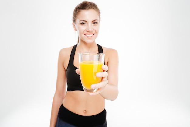 Uśmiechnięta ładna kobieta fitness pokazująca szklankę soku pomarańczowego na białym tle