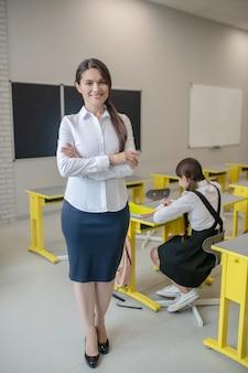 Uśmiechnięta ładna kobieta na wysokich obcasach w białej bluzce stojącej w klasie i uczennica przy biurku