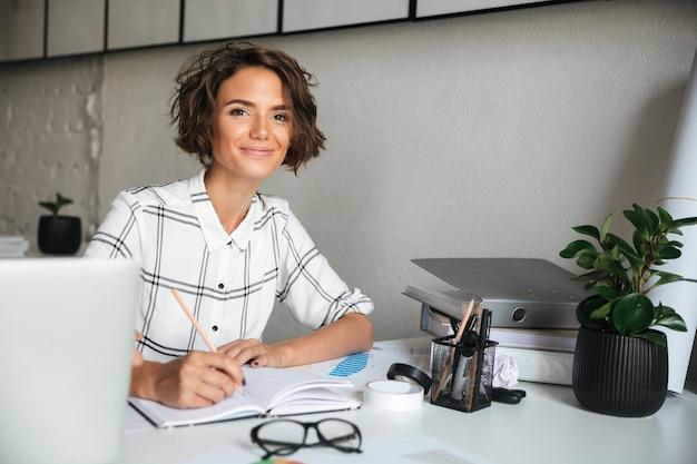 Uśmiechnięta ładna kobieta pracuje stołem