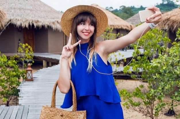 Uśmiechnięta ładna kobieta robi autoportret przez telefon komórkowy podczas jej tropikalnych wakacji w tajlandii. letnie jasne niebieskie ubrania ^ modny słomkowy kapelusz i torba. czerwone usta. wesoły nastrój.
