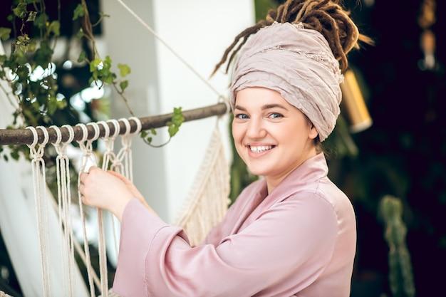 Uśmiechnięta ładna kobieta robi makramy tkackie