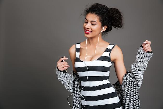 Uśmiechnięta ładna kobieta słucha muzyka z słuchawkami