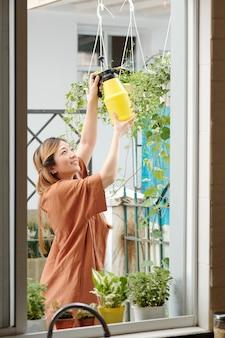 Uśmiechnięta ładna kobieta spryskuje kwiaty i rośliny na podwórku swojego domu