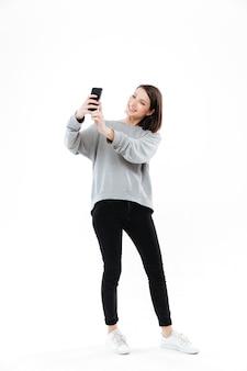 Uśmiechnięta ładna kobieta stoi selfie na telefonie komórkowym i bierze