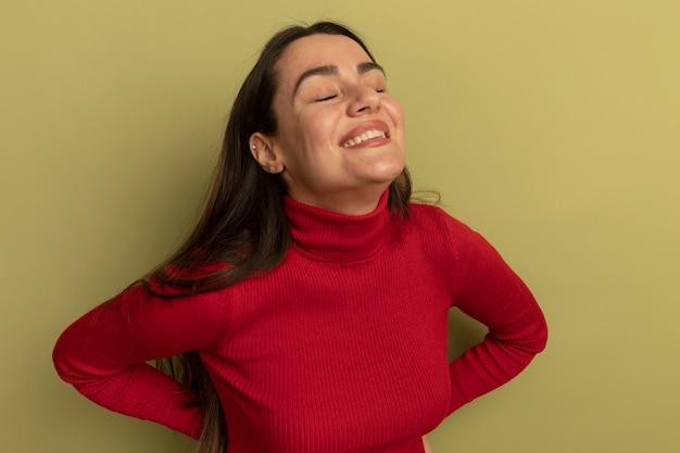 Uśmiechnięta ładna kobieta stoi z zamkniętymi oczami na białym tle na oliwkowej ścianie