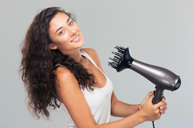 Uśmiechnięta ładna kobieta suszy włosy