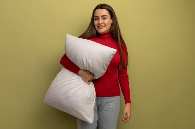 Uśmiechnięta ładna kobieta trzyma poduszkę na białym tle na oliwkowej ścianie