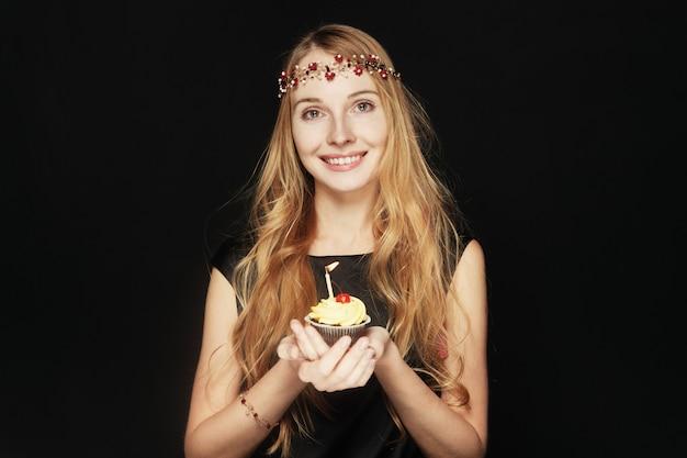 Uśmiechnięta ładna kobieta trzyma urodzinową babeczkę