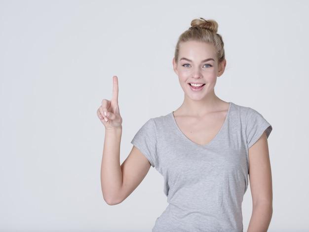 Uśmiechnięta ładna kobieta wskazując palcem na szarym tle. patrząc na aparat