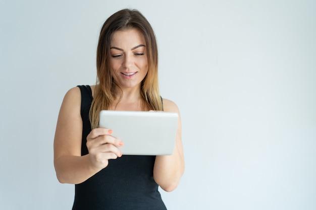 Uśmiechnięta ładna kobieta wyszukuje na pastylka komputerze. lady czytanie wiadomości na tablecie.