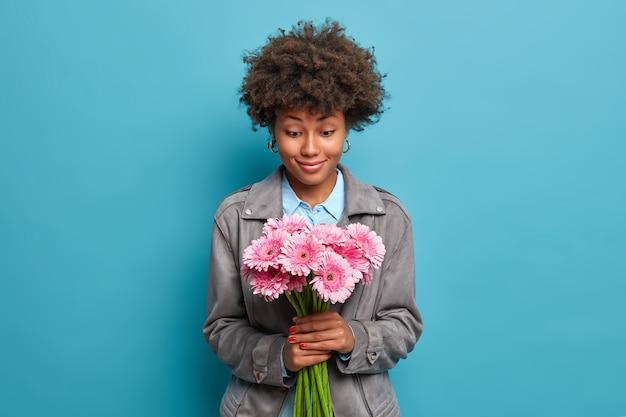 Uśmiechnięta ładna kobieta z naturalnymi kręconymi włosami radośnie patrzy na bukiet gerbera daisy