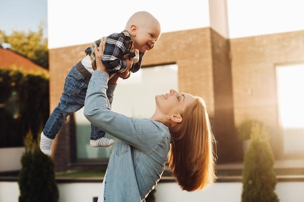 Uśmiechnięta ładna matka trzyma syna w dłoniach podczas zabawy