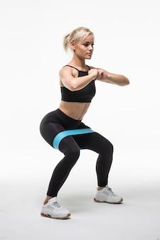 Uśmiechnięta ładna młoda blondynka robi różne ćwiczenia aktobatyczne rozciągające się na rękach i nogach na białym tle