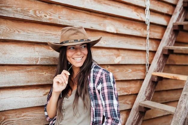 Uśmiechnięta ładna Młoda Kobieta Cowgirl W Kapeluszu Stojąca W Pobliżu Domu Premium Zdjęcia