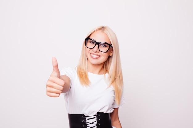 Uśmiechnięta ładna młoda kobieta pokazuje kciuki do góry na białym tle