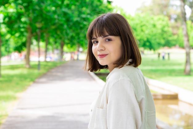 Uśmiechnięta ładna młoda kobieta pozuje przy kamerą w miasto parku