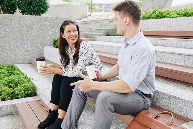 Uśmiechnięta ładna młoda kobieta rasy mieszanej, patrząc na współpracownika opowiadającego ciekawą historię, gdy siedzą na zewnątrz